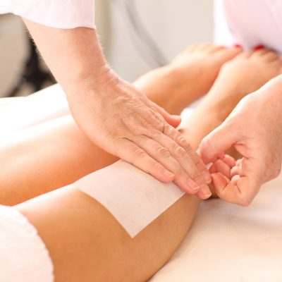 Woman getting her legs waxed at a beauty clinic.